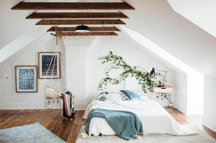 Attic bedroom with hanging chairs and plants